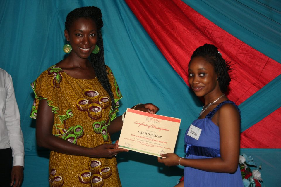 Giving a certificate of completion to a student at the Emerge Leadership Weekend.