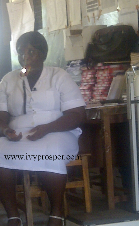Midwife in Kpalbe, Northern Region of Ghana, demonstrates using flashlight in her mouth.